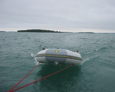 Photo: Zodiac dinghy in tow leaving Drummond Island, Michigan. Credit: L. Borre.