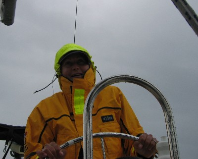 "Photo: Lisa Borre at helm of s/v ""About Time"" on Lake Superior. Credit: D.R. Barker."