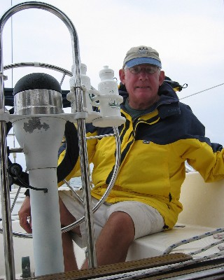 Photo: David R. Barker at the helm of s/v About Time ion Lake Ontario, 2004. Credit: L. Borre.
