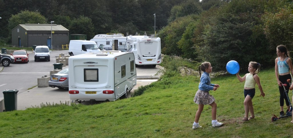 Girls playing on grass verge, next to trailers on a site