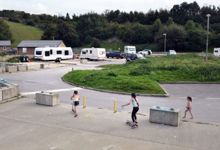 Picture of girls on skateboard and scooters on a caravan park`