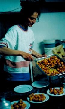 woman at the church making loukoumades (honey puffs)