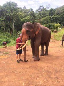 Grant hugging an elephant at Patara elephant farm