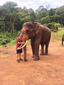 Grant hugging an elephant at Patara elephant farm