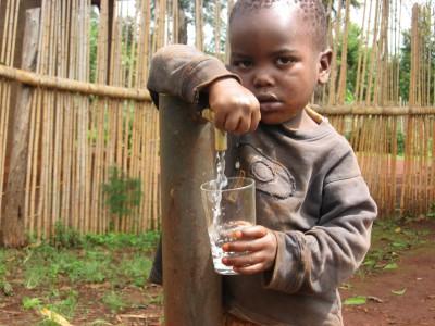 Enfant se désaltérant avec de l'eau potable. Cameroun.