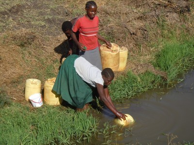 Women drawing dirty water. Kenya.