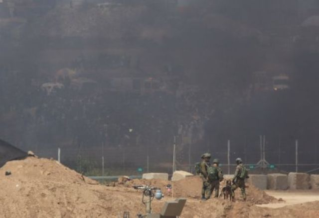 Soldiers stand in front of the Gaza border fence, facing a wall of black smoke raising from the burning tires, April 6, 2018