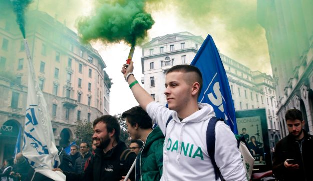 The League party's activists hold flares as they arrive to attend a rally by party's leader Matteo Salvini, in Milan, Italy, Saturday, Feb. 24, 2018.