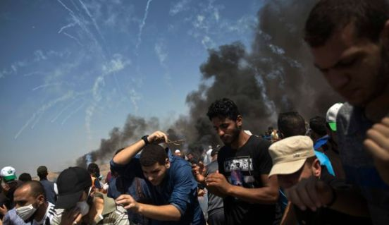 Tear gas canisters fired by Israeli troops fall over Palestinian protesters at the Gaza Strip's border with Israel, Friday, June 8, 2018.