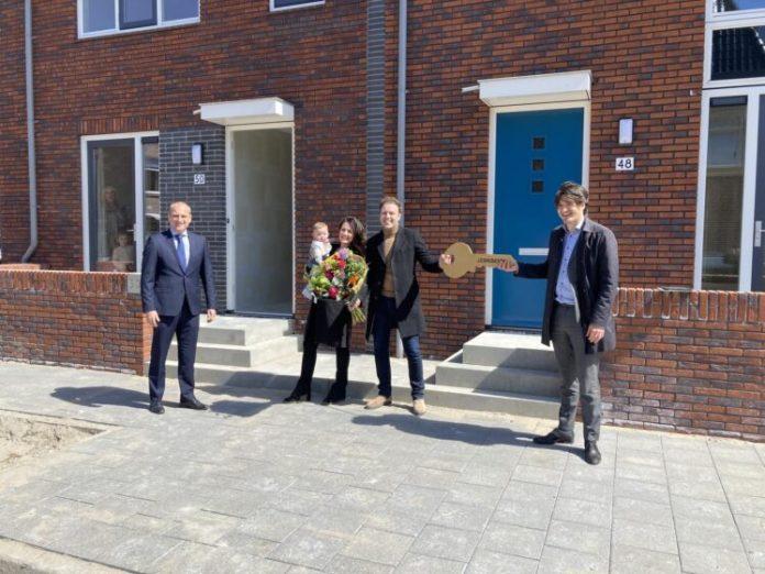 Wethouder Floor Roduner (rechts) overhandigt in het bijzijn van Peter Heuvelink, directeur AM Noordwest, de sleutel aan de nieuwe bewoners.
