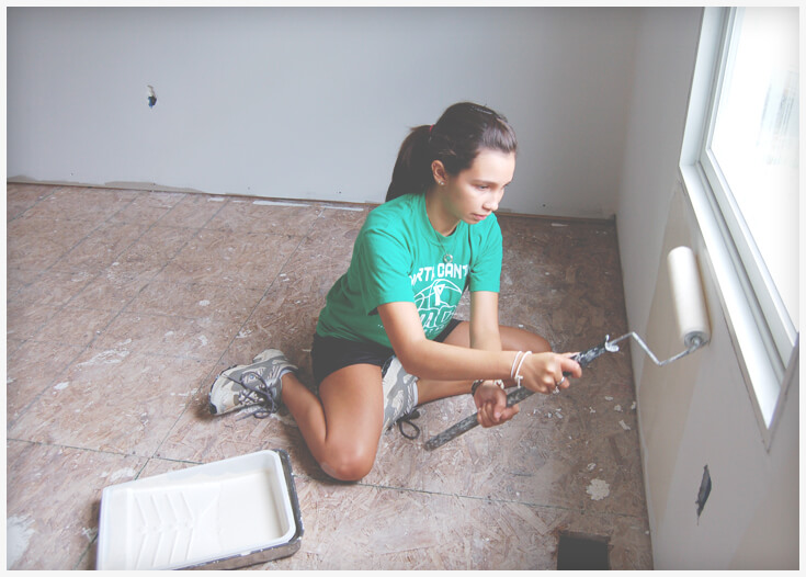 Volunteer paint a new decent, affordable home