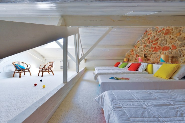The children's dormitory in the attic is a clean and bright white-painted space with mix-and-match strong colours used for beds, pillows and lamps.