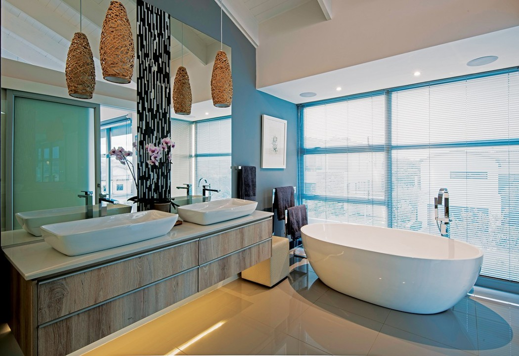 The main en suite bathroom has a freestanding bath cantilevered out over the edge of the building in a frameless glass corner facing towards the mountain views.