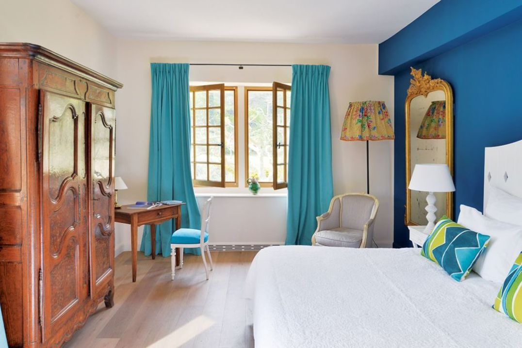 The first of the two blue-walled bedrooms is quite grand in scale, with an antique wardrobe, gilt-framed mirror and two chairs reupholstered in complementary blues and greys. The bedside lamps and tables complement the bright white of the headboard and bed cover. The en suite bathroom contrasts with very subdued, white and off-white floor and walls.