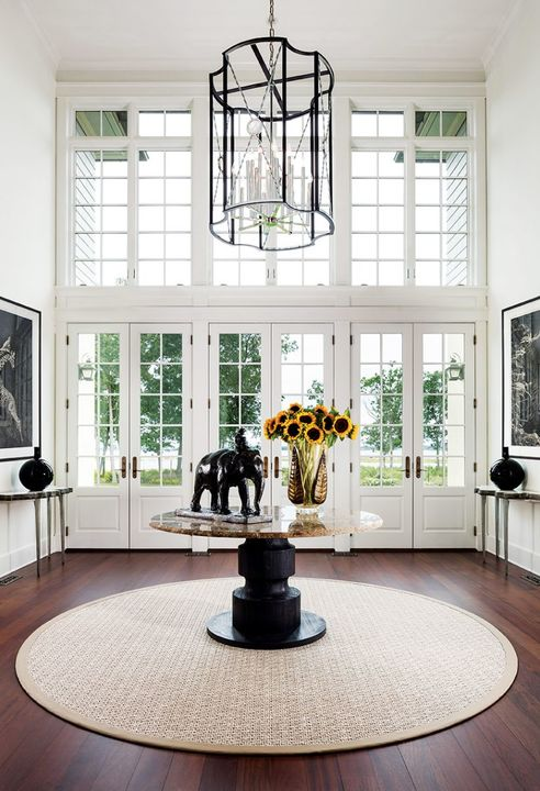 The double volume glamour of three metre high ceilings introduces one to the elegant progression of contiguous rooms with water views. A custom-made, overscaled lantern in iron, steel and rock crystal adds drama. A bronze elephant by Roger Godchaux is featured atop a McGuire centre table.