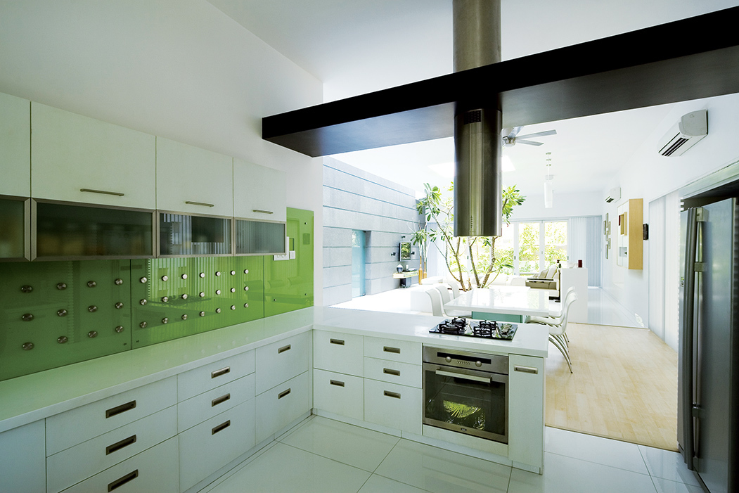 The kitchen platform and the dining table are finished with solid surface material to create a homogenous effect.