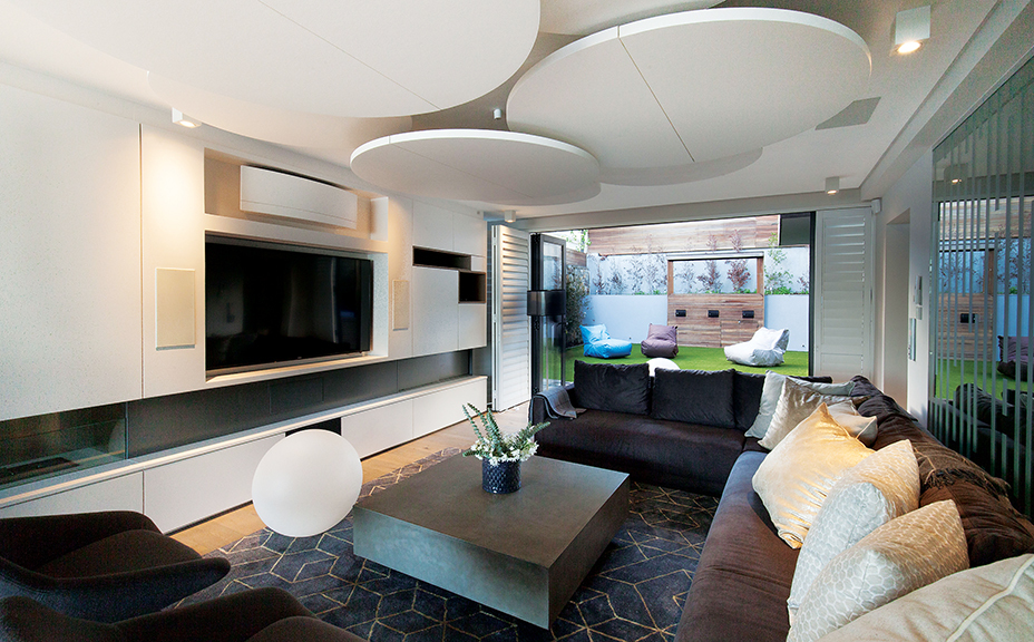 The joinery was designed by the interior architects to reflect the linearity of the horizon while being innovative in using new materials, such as the circular acoustic panels suspended from the ceiling of the TV area