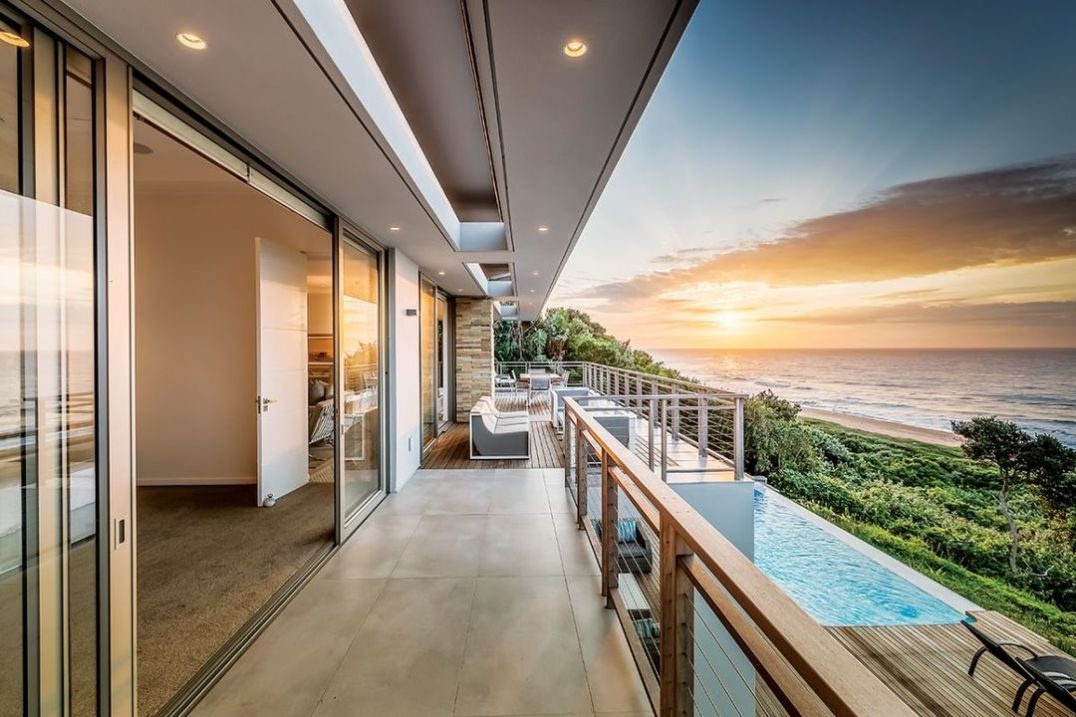 The covered terrace is at the rear of the home, on both top and bottom floors, and has two sets of multiple sliding / folding glass doors to access the other living areas.