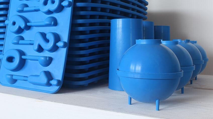 Grupo de moldes de plástico en color azul para hacer velas de cumpleaños y velas redondas.