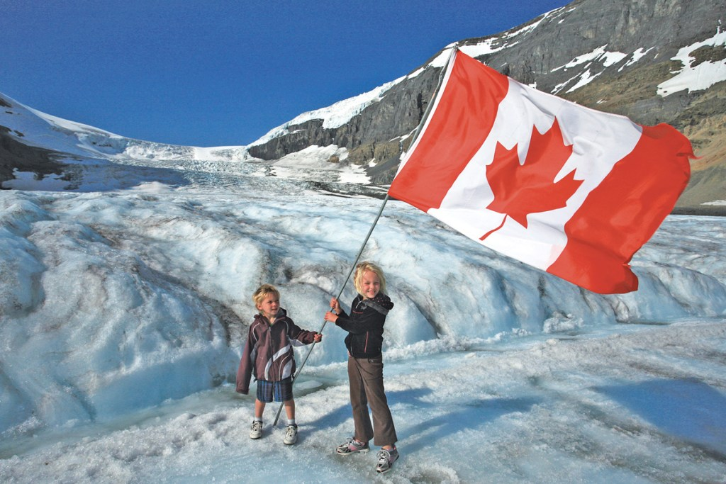 two kids standing on ice holding a canadian flag