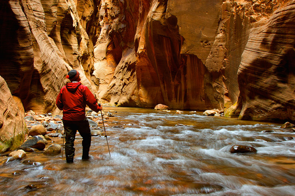 hiker standing in water with canyons on either side
