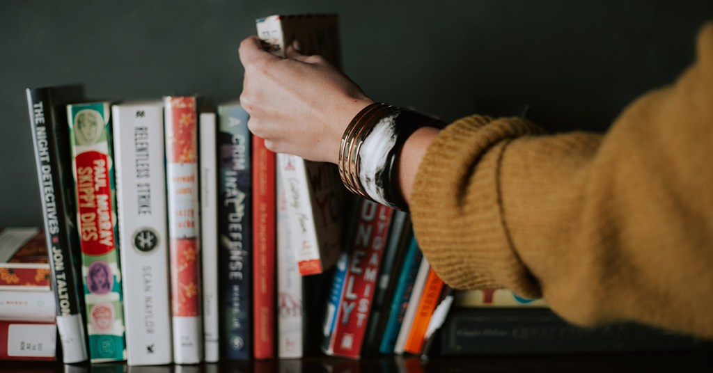 Novel Suspects Featured Image Bookshelf Hand