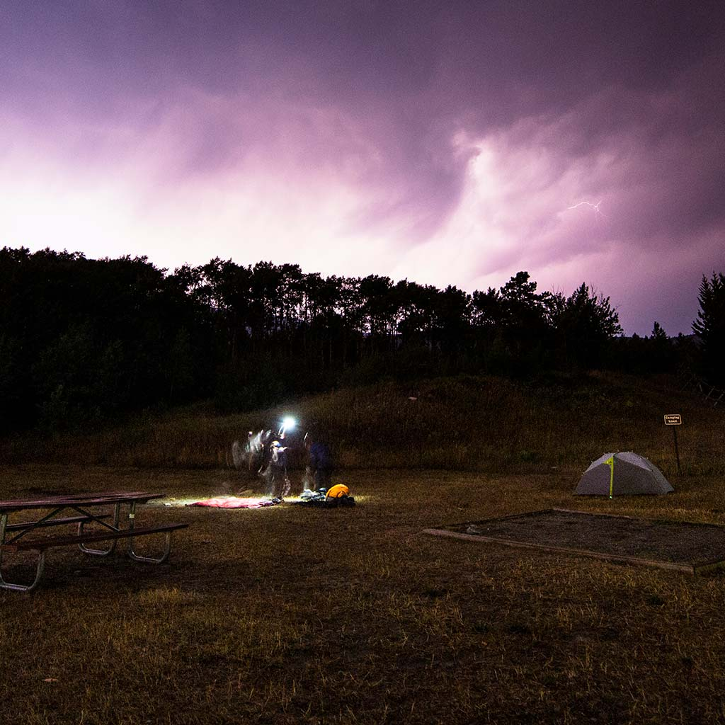 Lighting strikes, turning the sky white purple and pink. A tent and a picnic table are illuminated in the wide open space, trees line the space in the distance.