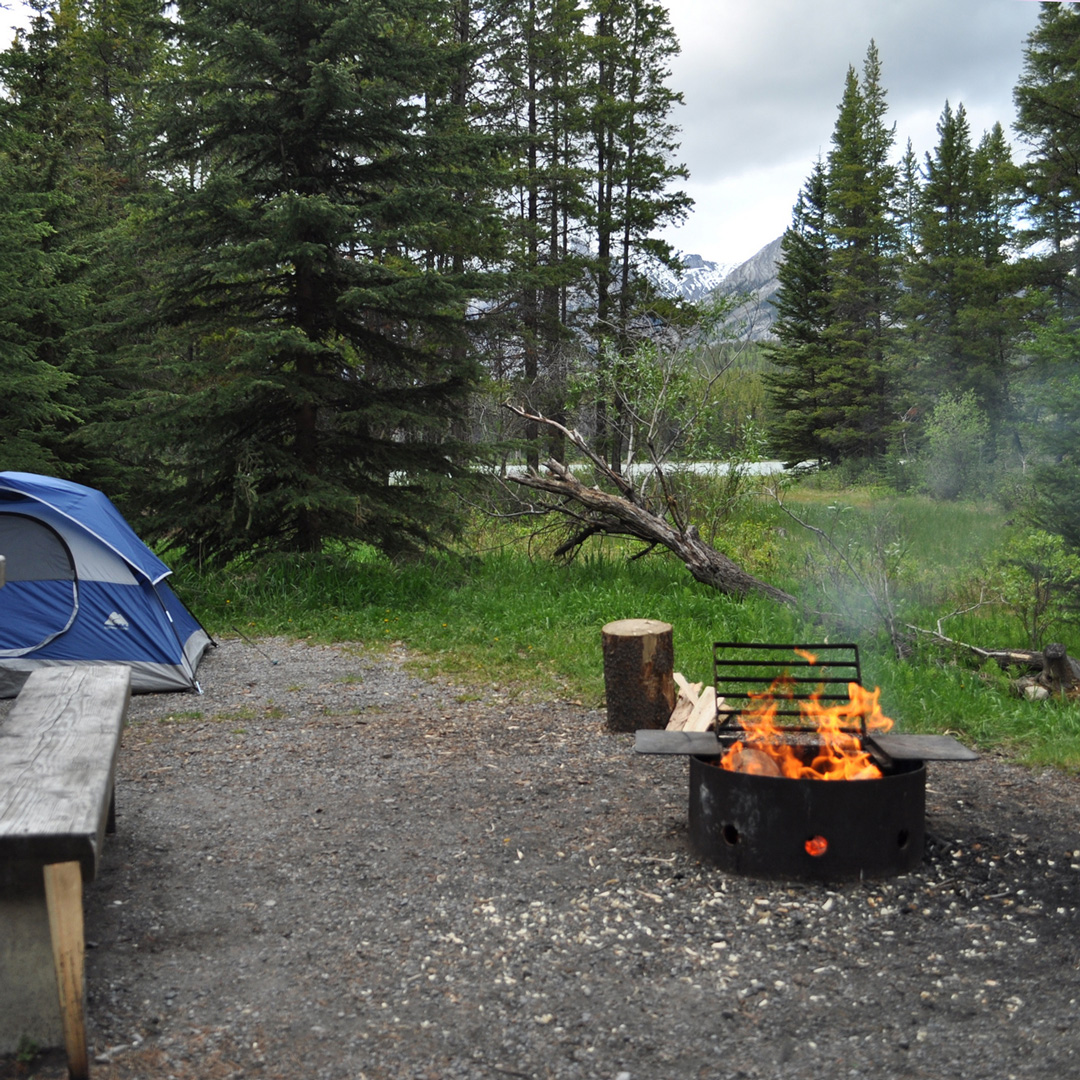 wood burning and tent at campsite in Banff