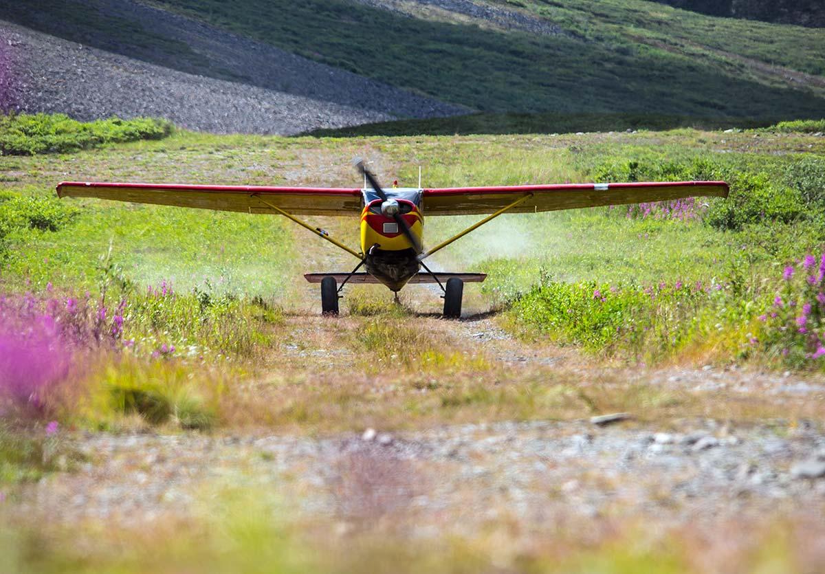 An Alaskan bush plane readies for takeoff in a grassy field.