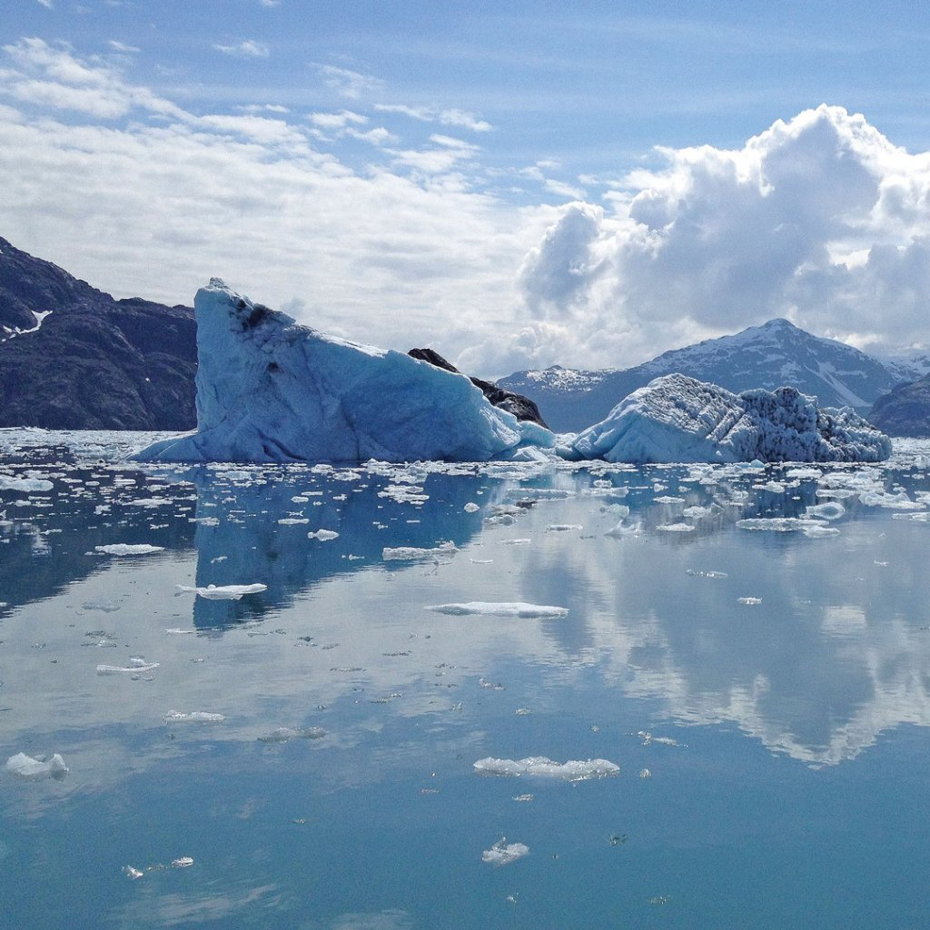glaciers reflected in calm water