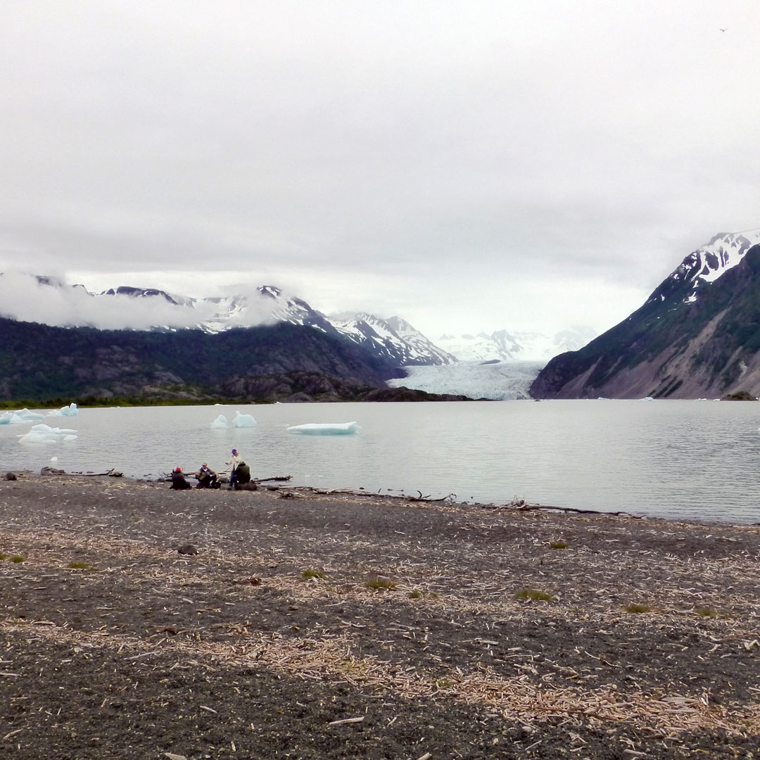 hikers sitting on the beach near the Grewingk Glacier lake