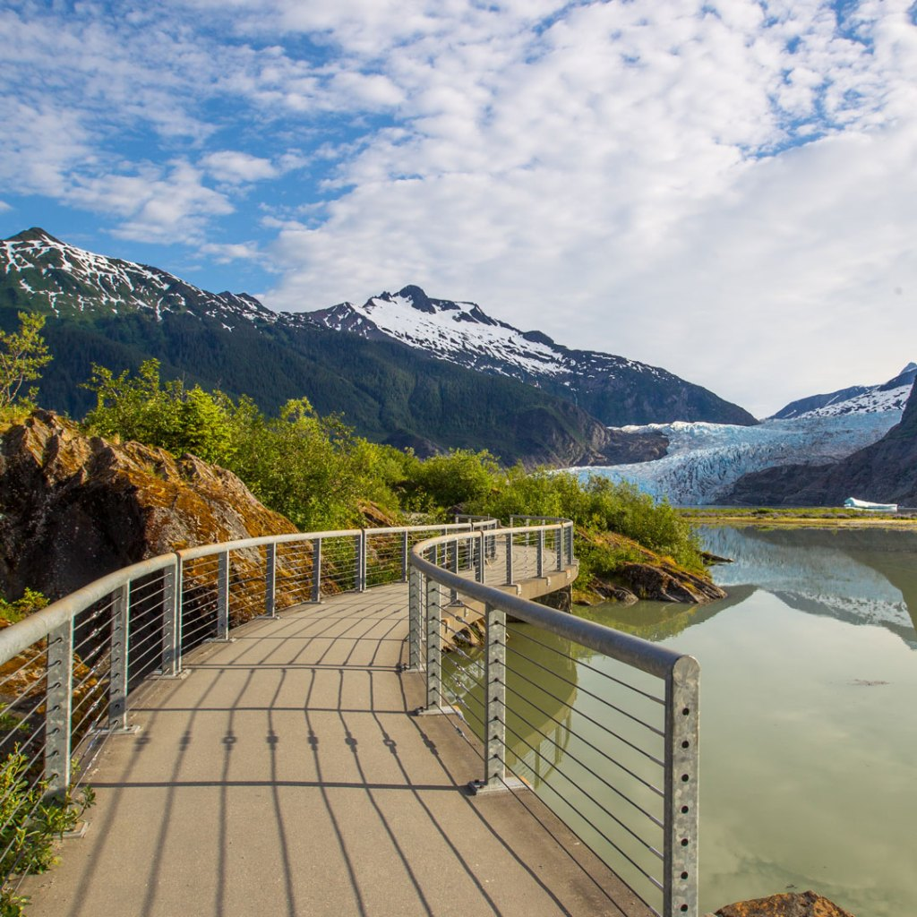 a concrete pathway leading to a glacier and mountains