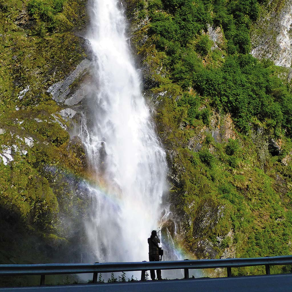 A woman stands and admires the cascading Bridal Falls from a lookout point