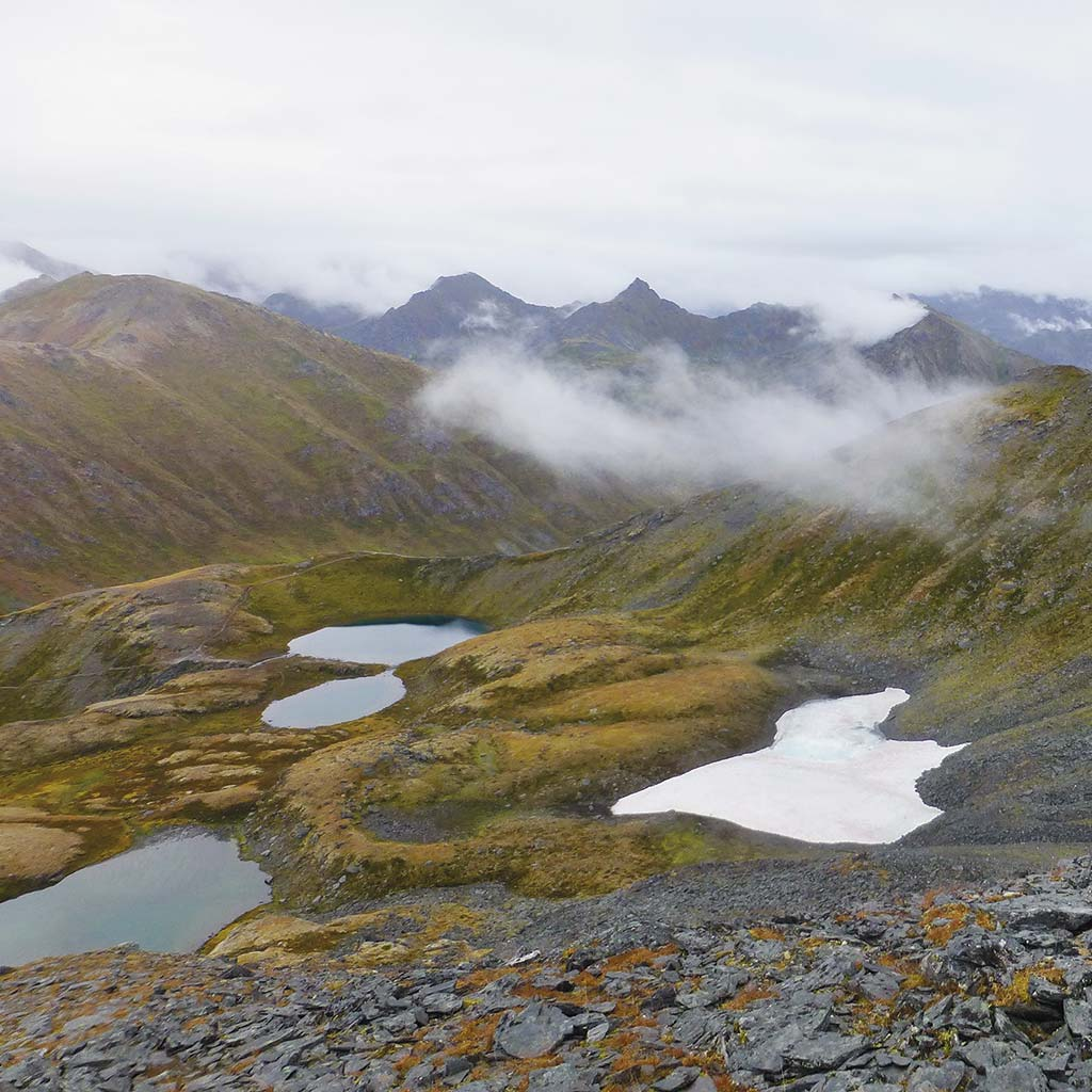 View of Hatcher Pass featuring grass, four small lakes, and some low clouds