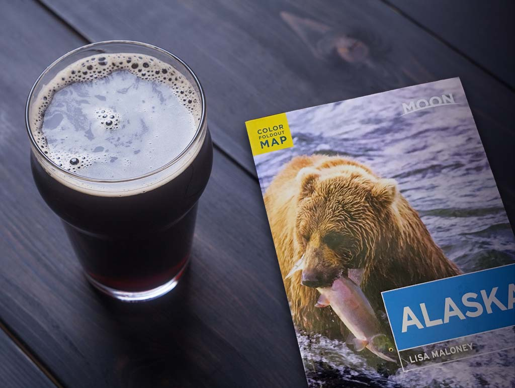 A stout beer sits atop a table next to a copy of the Moon Alaska guide book