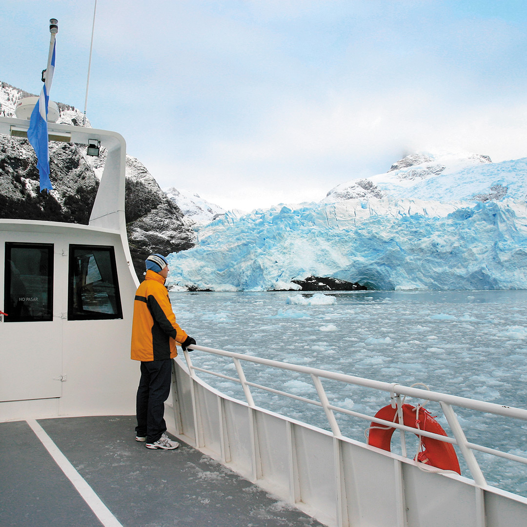 tourist on a boat gazing at Upsala glacier in Los Glaciares national park