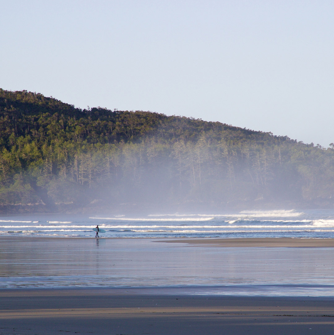 a surfer walks on the beach in Tofino BC