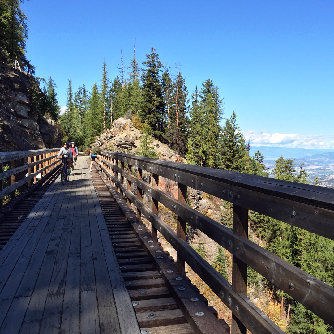 cyclists riding bikes along kettle valley railway with views of British Columbia