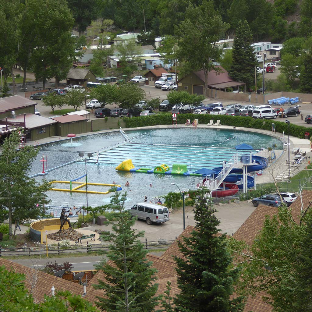 Ouray hot springs is pictured: it looks like a roundish pool and is divided into three sections, one of which has equipment for kids to play on