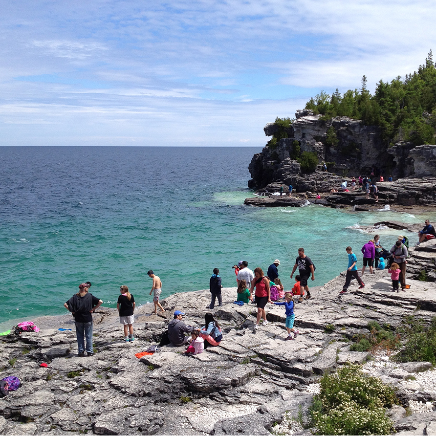 People stand at the edge of a rocky bank, overlooking blue water at Bruce Peninsula National Park