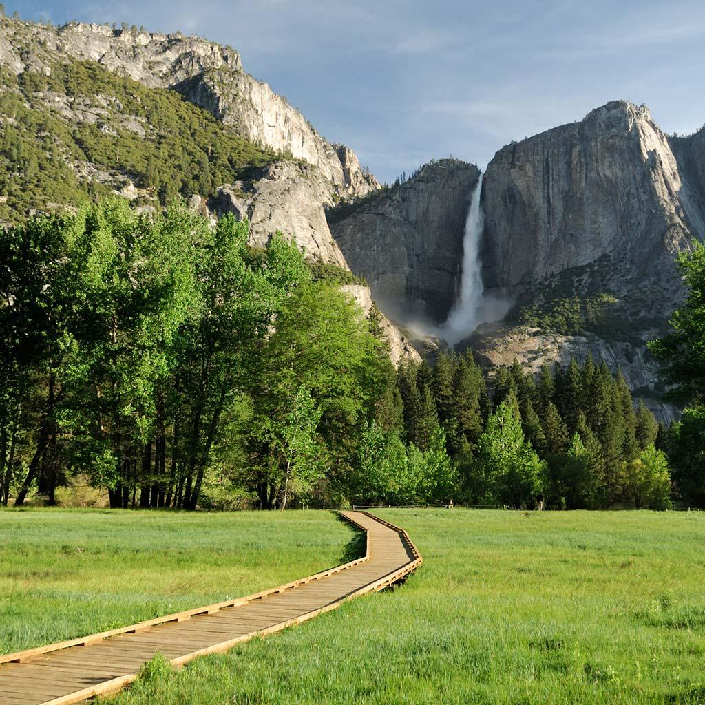 boardwalk in yosemite valley leading toward a waterfall