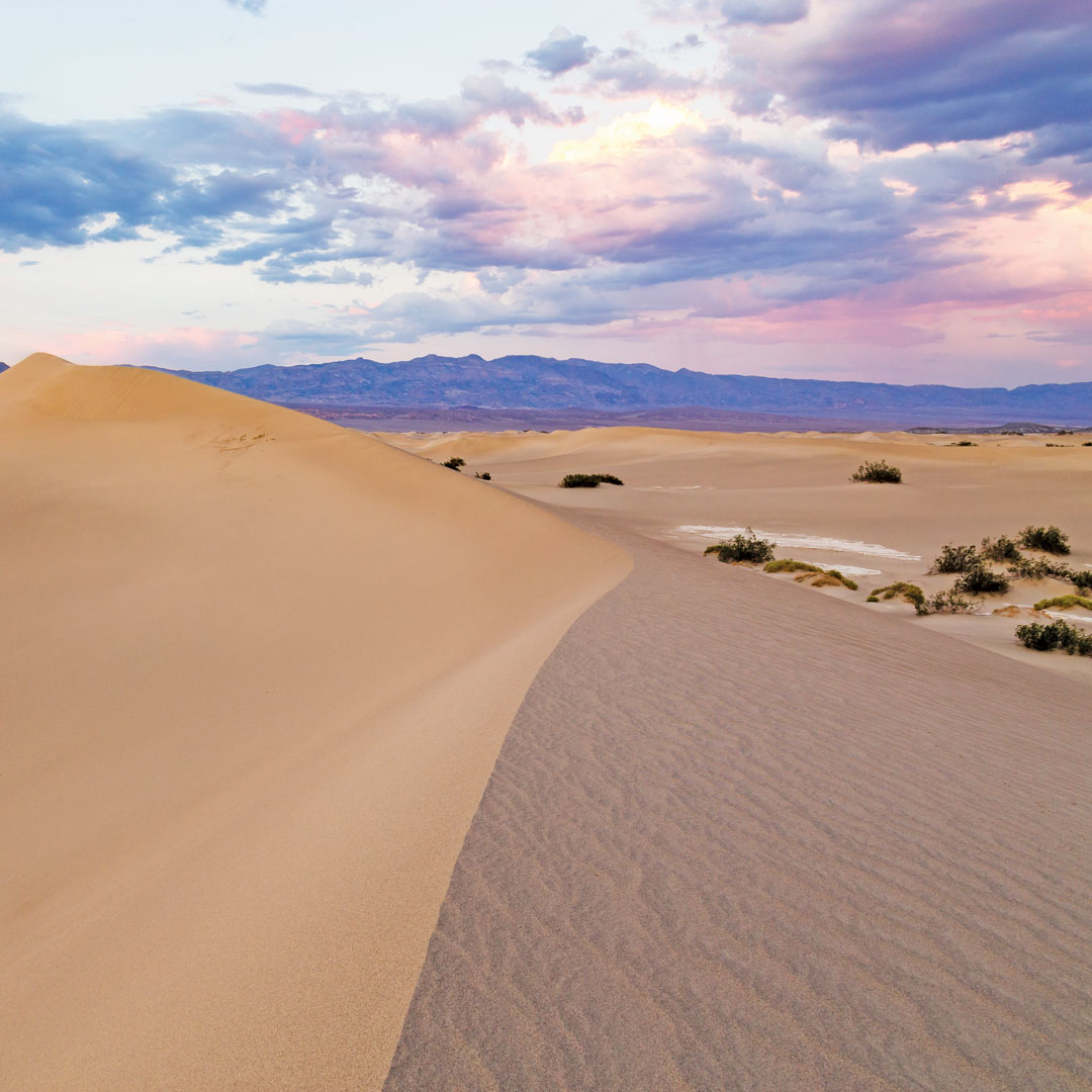 sky turning purple and pink at sunset over sand dunes in Death Valley