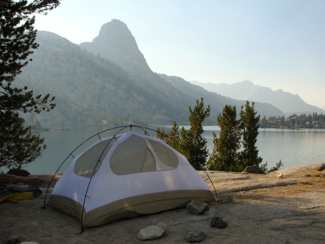 At lakeside, a dome tent is pitched amongst coniferous trees.
