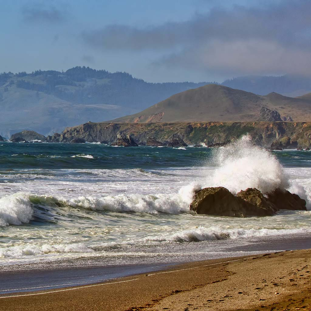 Looking out Wrights Beach towards the hills and cliffs in the distance. Waves crash onto shore and onto a boulder close to the shoreline