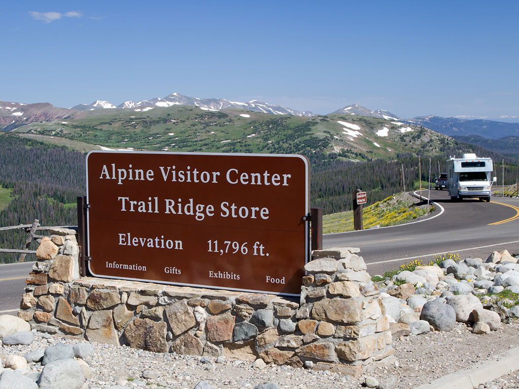 Alpine Visitor Center sign next to a winding road