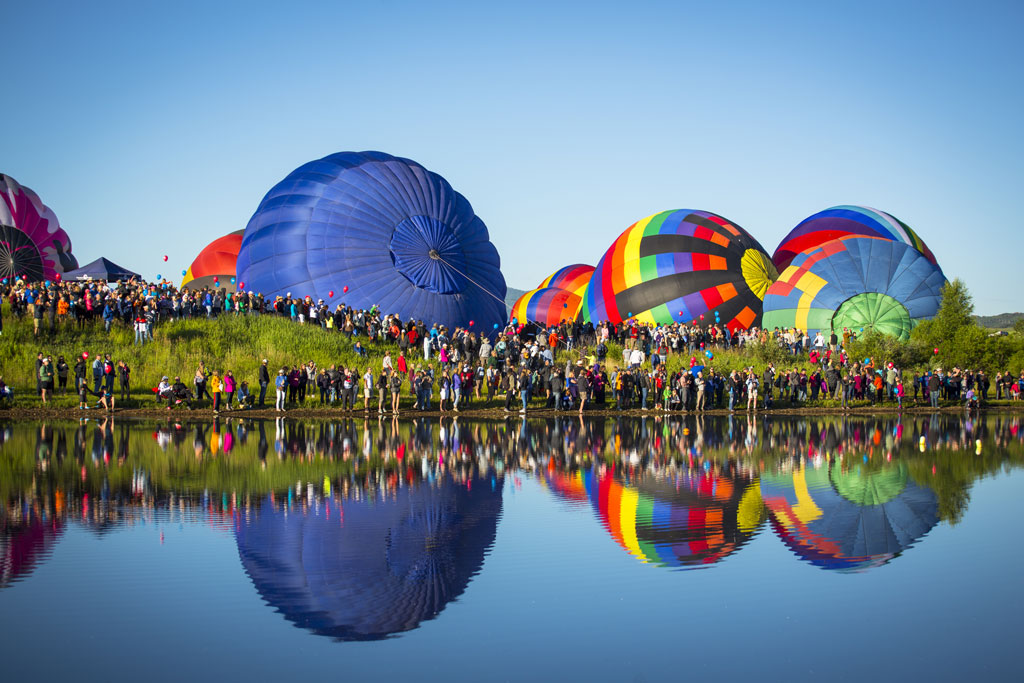 hot air balloons near a body of water on a sunny day