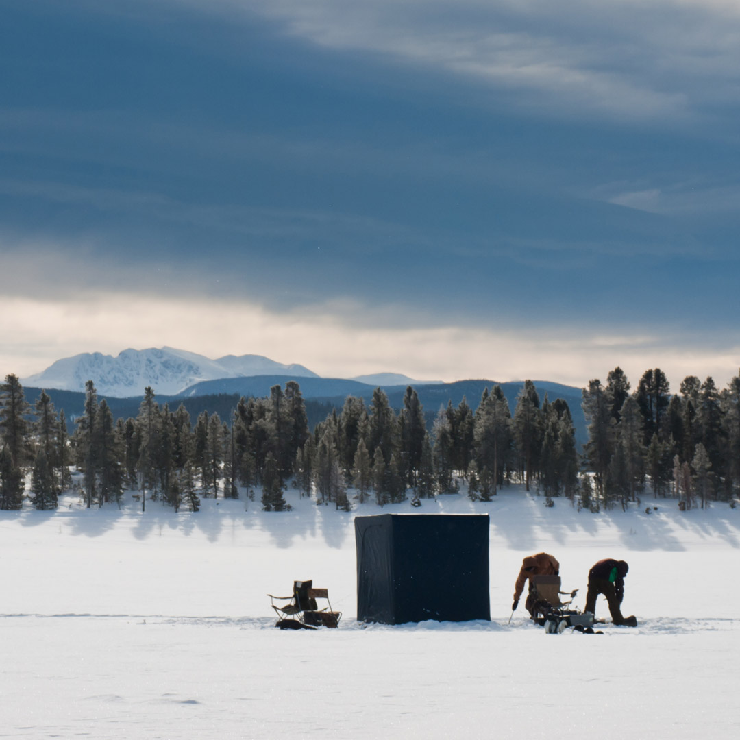 two people out on a frozen over lake in Colorado going fishing