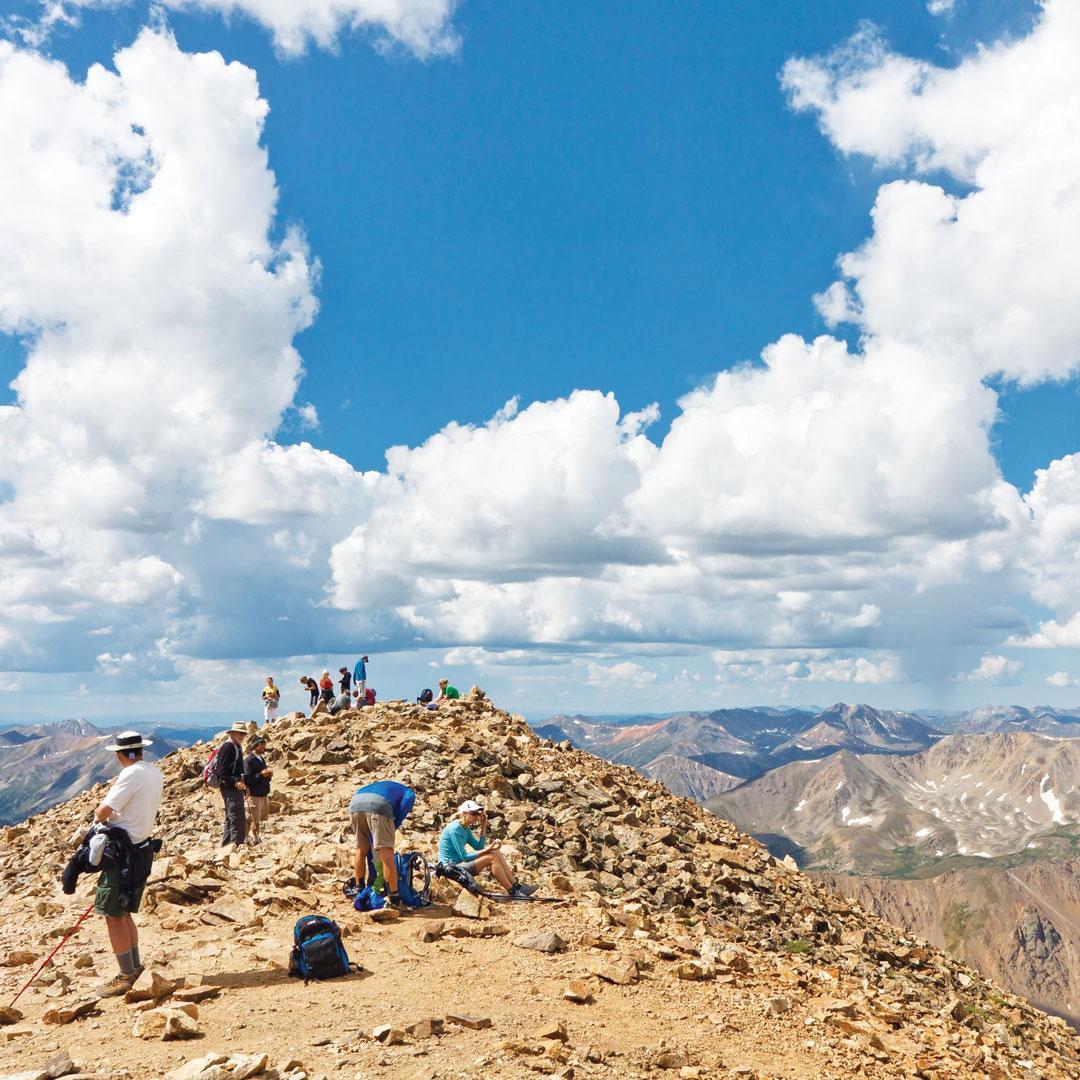 hikers atop the peak of Mount Elbert