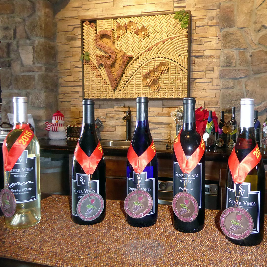 award metals hang on bottles of wine at Silver Vines Winery