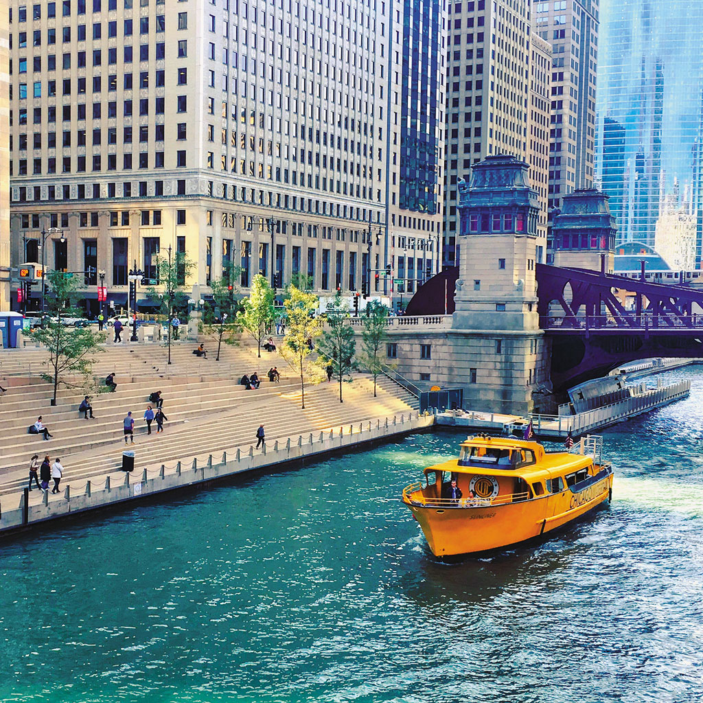 a yellow boat on the river in Chicago surrounded by tall buildings